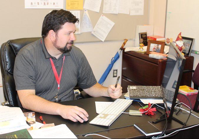 Counselor+Scott+Olsen+works+at+his+desk.++Olsen+works+in+effort+to+help+students+get+into+college.