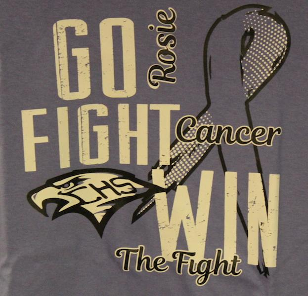 Nearly+%24570+was+raised+for+teacher+Justin+Rosenblad%E2%80%99s+fight+against+stomach+cancer+through+the+sale+of+specialized+T+shirts+in+honor+of+the+coach+and+senior+night+.+