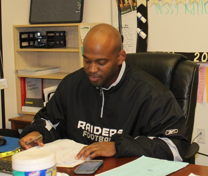 Damein Roache sits at his desk doing some paperwork.  SUN offeres new after school opportunities for students.