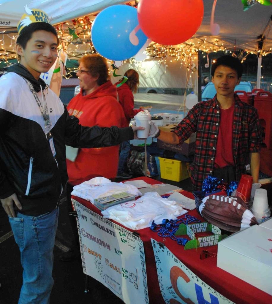Kevin Luc receives a hot chocolate from the choir booth during the Eagle Bite homecoming tailgate.