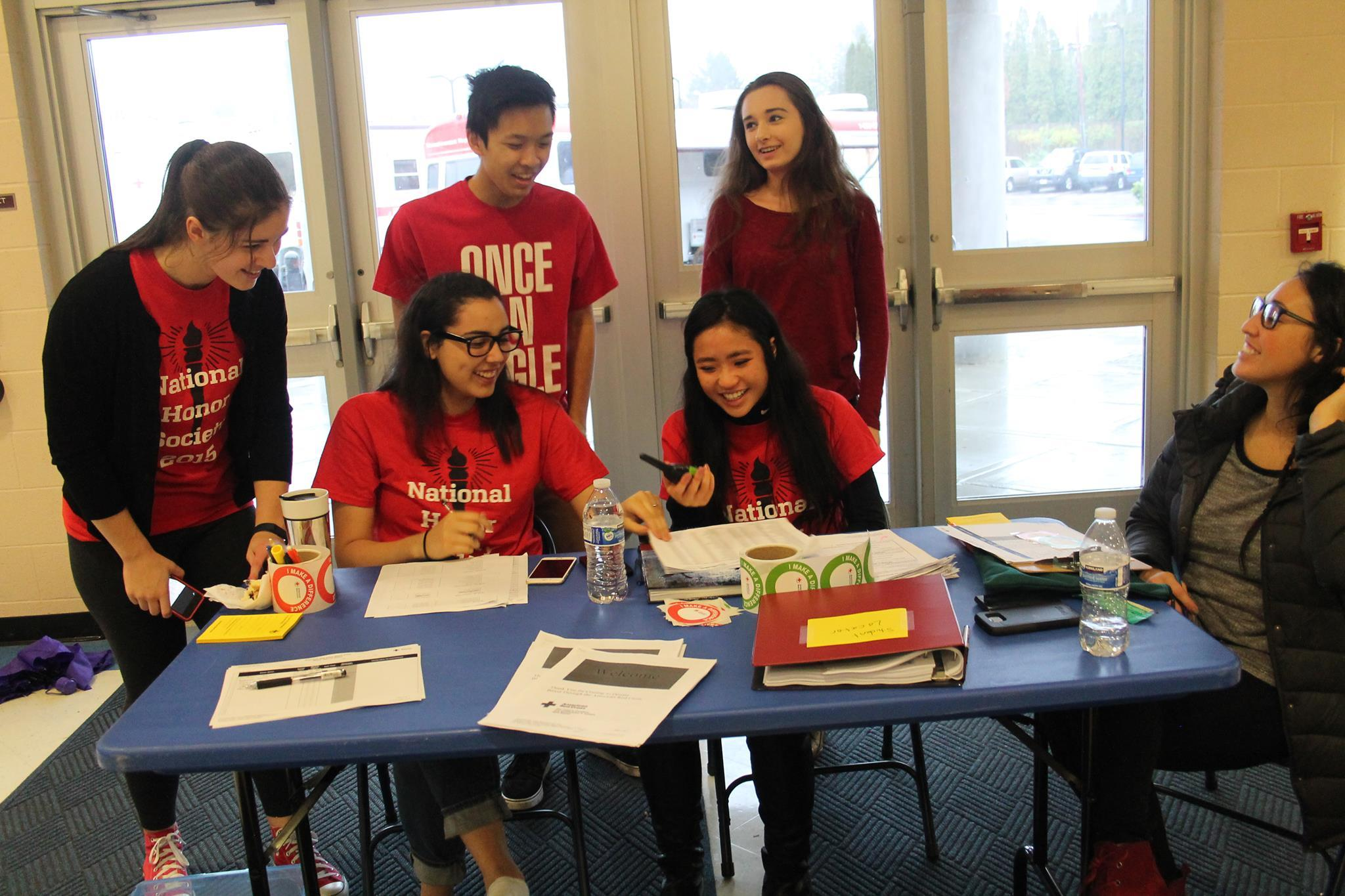 NHS Officers Laura Popescu, Monica Angelecio, and Linh Tran having fun signing students up.