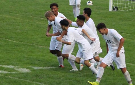 The boys' team celebrates after a goal in a home game.