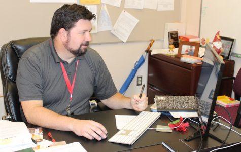 Counselor Scott Olsen works at his desk.  Olsen works in effort to help students get into college.