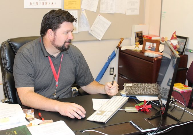 Counselor Scott Olsen works at his desk.  Olsen works in effort to help students get into college.