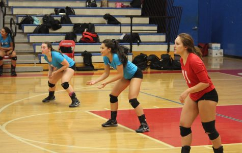 Rhyan Becker, Trina Varney, and Hannah Bowlen get ready for the ball during a home game.
