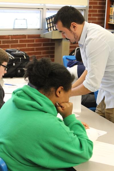 MeChA adviser Edgar Brambilia-Perez assists a student with school work.