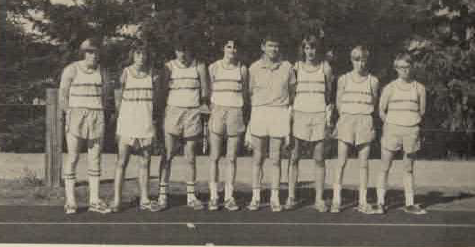 Hiram Crane (pictured in middle) stands with cross country team. Scanned from 1974 yearbook.