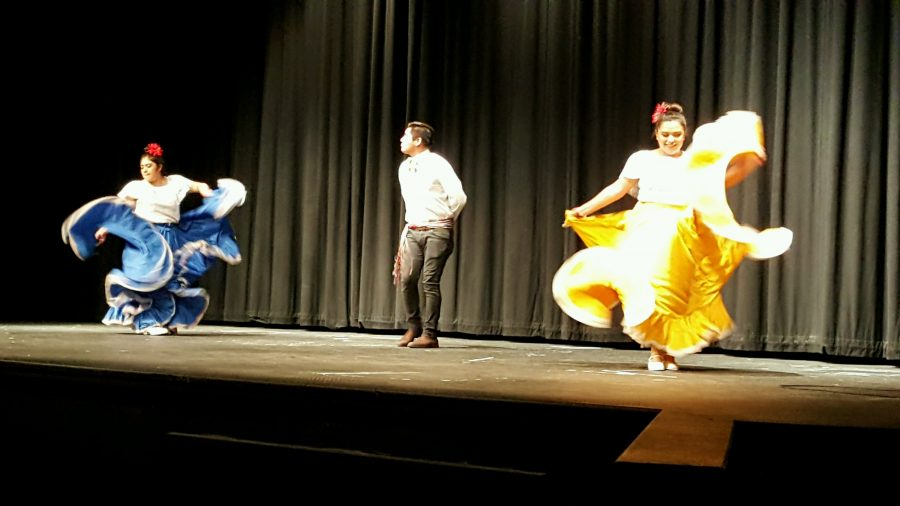 Centennial girls junior  Elva Mendez-Martinez (far left) and senior Eunice Moreno (far right) dance around guest Julio Perez in the first performance at the Multi-Cultural and Resources Night on Tuesday.    This was a traditional Mexican dance called