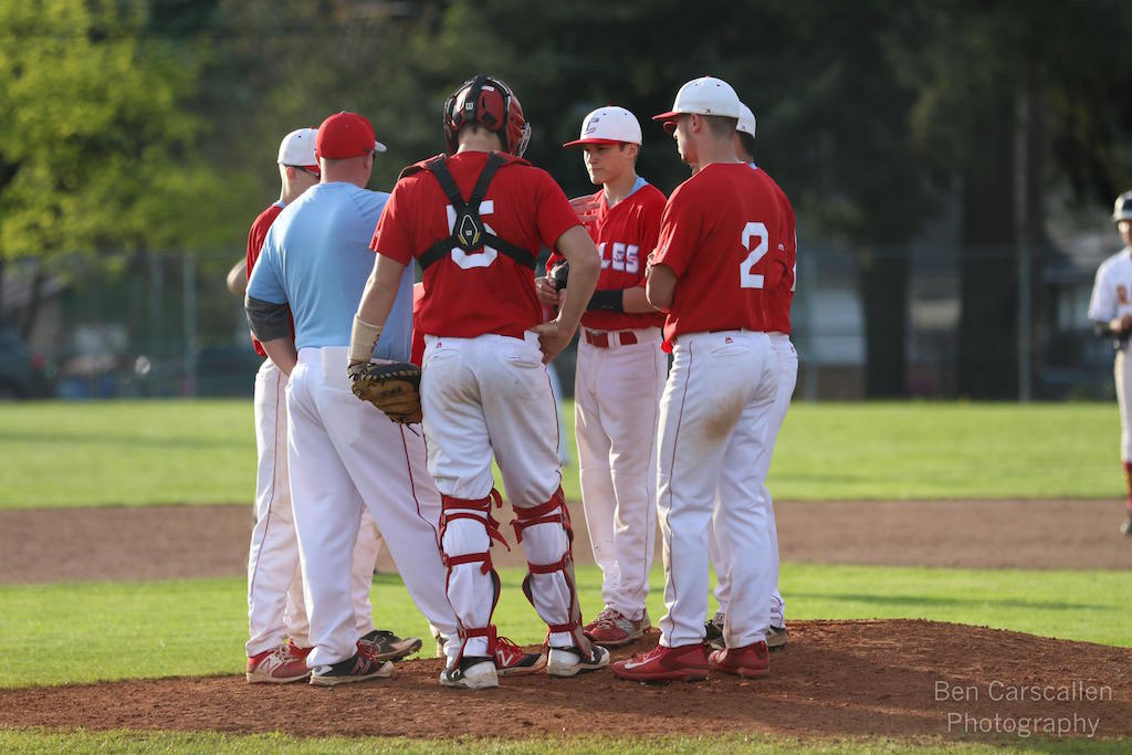 Head coach Kevin Christie meets with his infield during a game earlier this month.