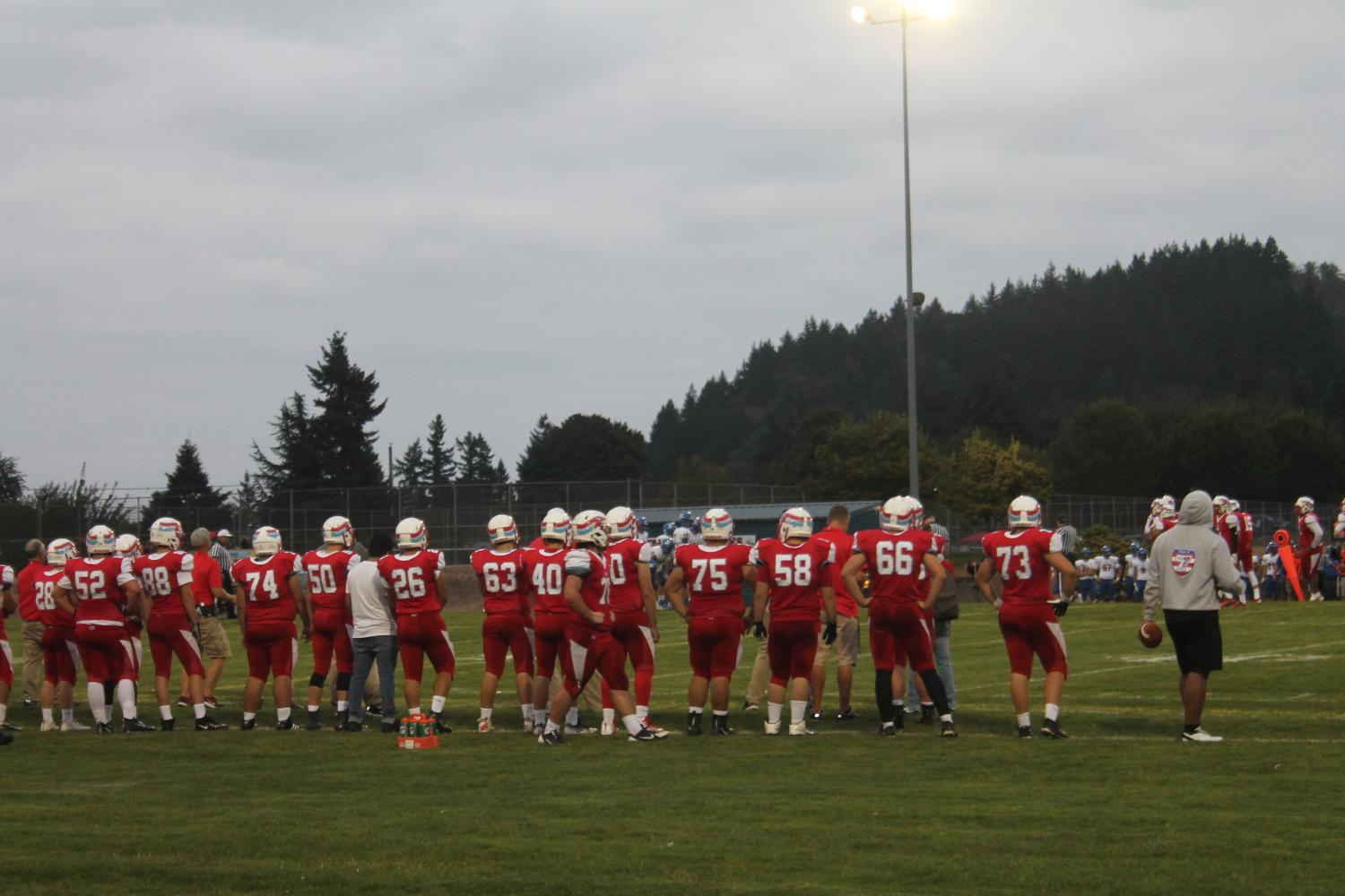 Several Eagle football players look on anxiously as the team plays last week against Newberg in a 56-27 loss to the Tigers.
