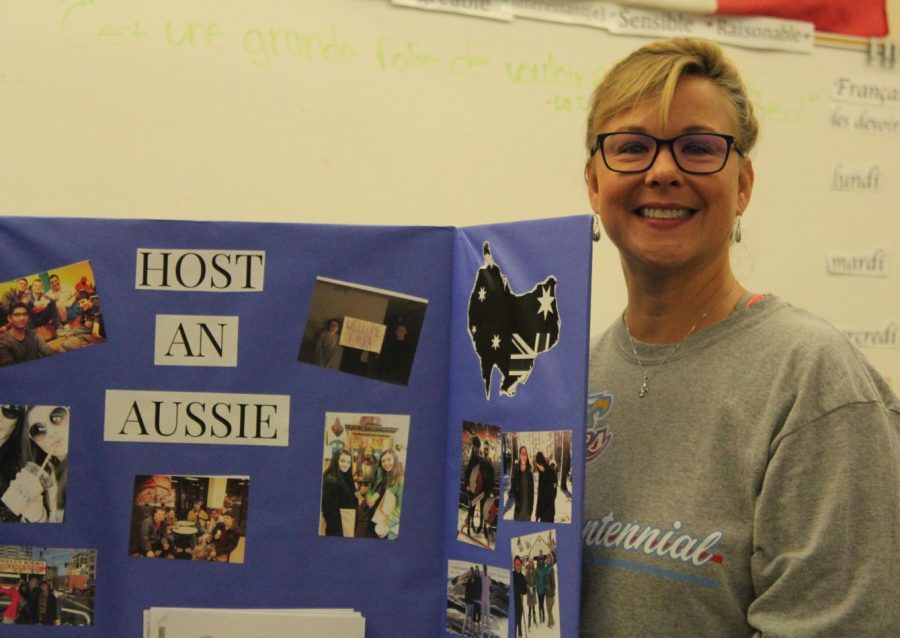 Rowena Poirier holding up an Australian poster board from last year. She is one of the main instructors in charge of matching up Australians with host families.