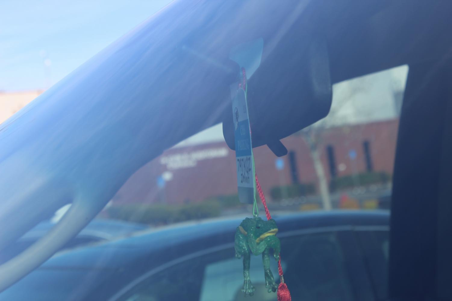 Parking passes hanging from cars parked in the lot. Parking passes are required in order to park.