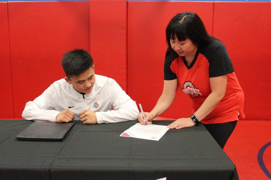 Kue's mom signs parent permission for the scholarships.