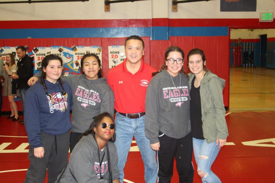 Center: Head girls wrestling coach Taz Lee and other girl wrestlers from 2017/18.